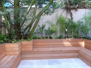 Dubbel gebruik van de ruimte; de zitbanken zijn tegelijk opbergplaats; de laurierstruik is gehandhaafd en ingepast in het ontwerp.