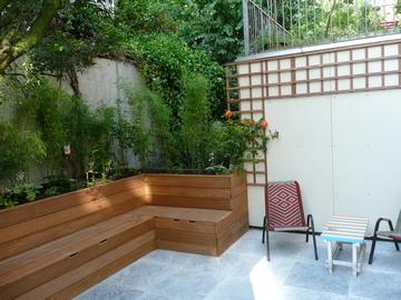 Het terras bestaat uit natuurstenen tegels met een lichtgrijze kleur om de kleine tuin zo licht mogelijk te houden.