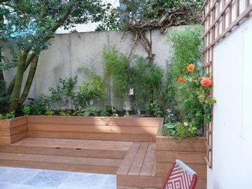 Om de betonnen achtermuur wat te camoufleren is pluimhortensia en bamboe geplant met op de voorgrond een aantal soorten vaste planten zoals elfenbloem, hartlelie, ooievaarsbek en zilverkaars.