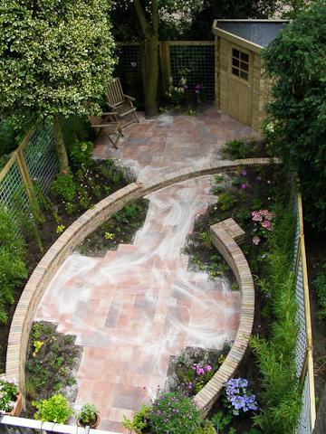 Zitmuurtjes in combinatie met opstapje naar terras vormen markante bogen door de tuin.