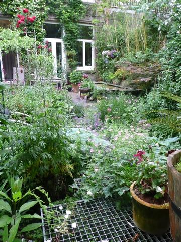 """Zicht vanaf het hoger gelegen terrasje achterin de tuin. Het tuinpad is van """"zwevende"""" roosters."""