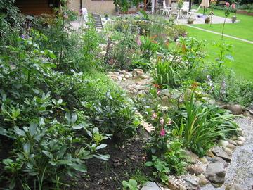 De beek stroomt over een lengte van 20 meter vanaf het hoger gelegen terrasje rechts achter in de tuin naar de forse vijver bij het huis.