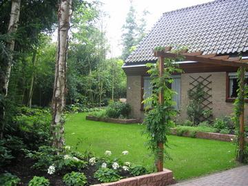 Een pergola met klimplanten als doorgang naar de tuin, weelderig beplante verhoogde borders, aansluitend bij het huis, zetten het huis in het groen.